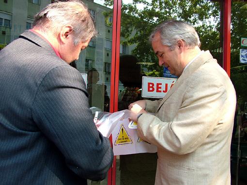 Szirbik Imre polgármester és Mészáros Zoltán vezérigazgató a Hunor Coop  Kála Áruházának bejáratára helyezi ki a Vedd és Védd a Szentesit emblémát 2009-ben.